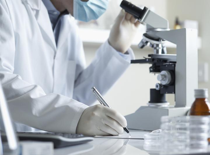 врач изучает мазок под микроскопом