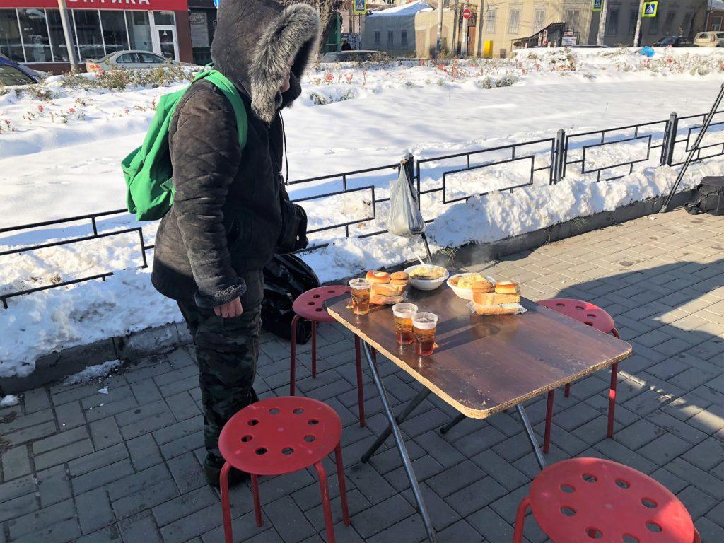 Получив еду, люди садятся застол, который волонтеры заботливо установили рядом спалаткой //Фото: Валерия Казарова