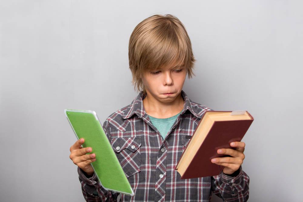 Мальчик с бумажной и электронной книгами //Фото с сайта tlum.ru